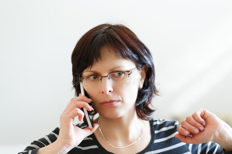 Vermoeide vrouwenvraag op middelbare leeftijd telefonisch stock afbeeldingen