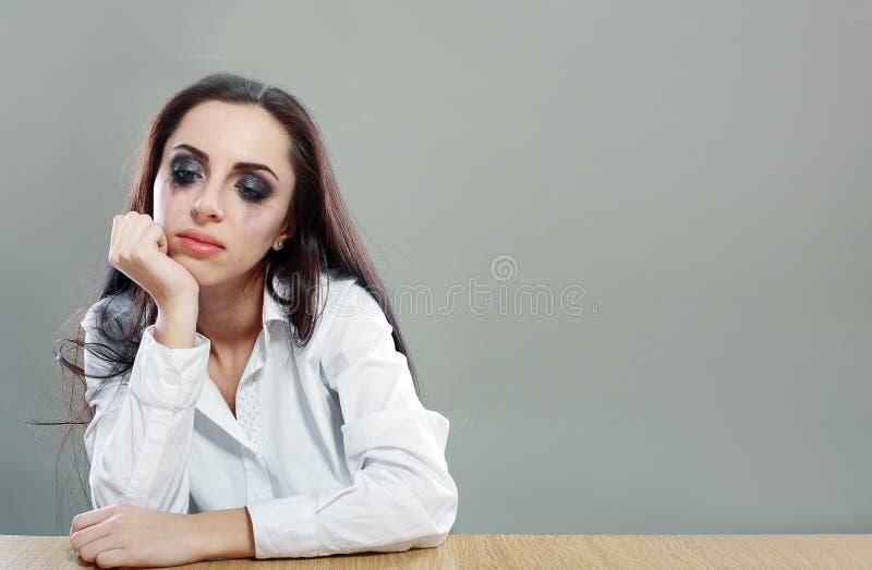 Vermoeide vrouwenzitting bij het bureau royalty-vrije stock afbeelding