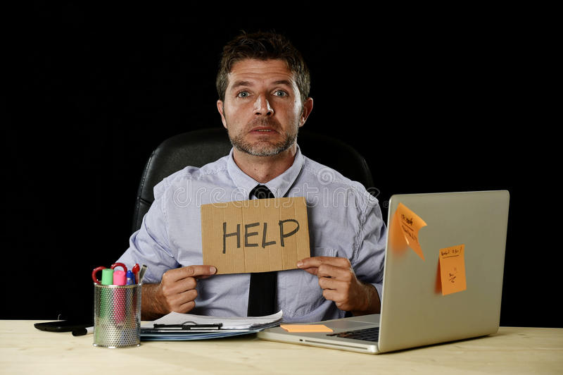 Vermoeide wanhopige zakenman die in spanning bij het teken werken die van de het bureauholding van de bureaucomputer om hulp vrag royalty-vrije stock foto's