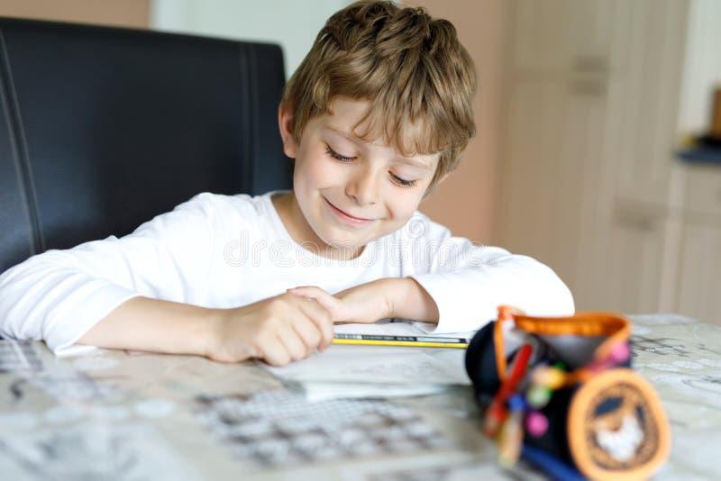 Vermoeide weinig jong geitjejongen die thuis thuiswerk maken bij de ochtend alvorens de school begint Weinig kind die oefening do royalty-vrije stock afbeelding