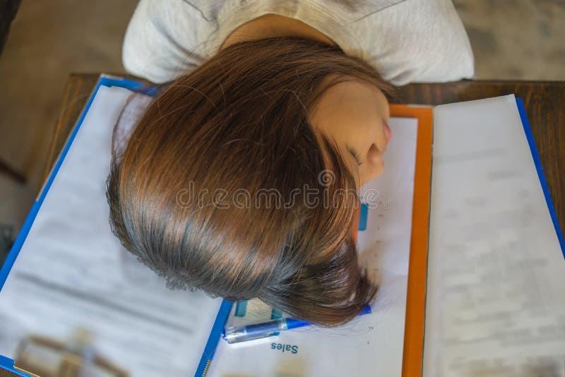 Vermoeide werknemersslaap op haar bedrijf` s rapporten royalty-vrije stock foto