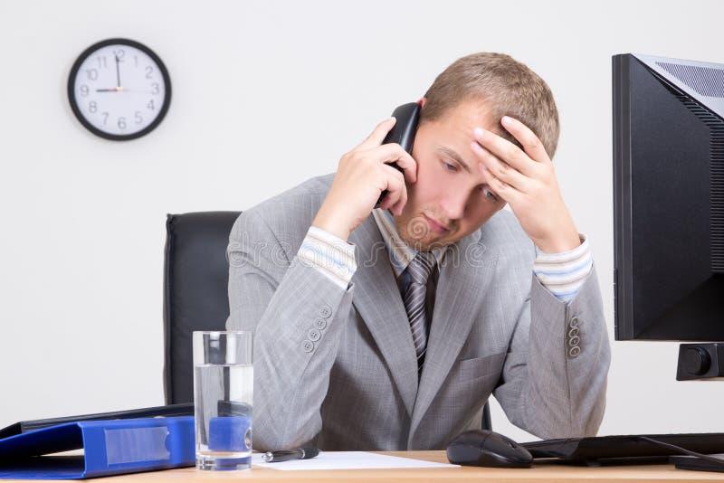 Vermoeide zakenman die op telefoon in bureau spreken royalty-vrije stock foto