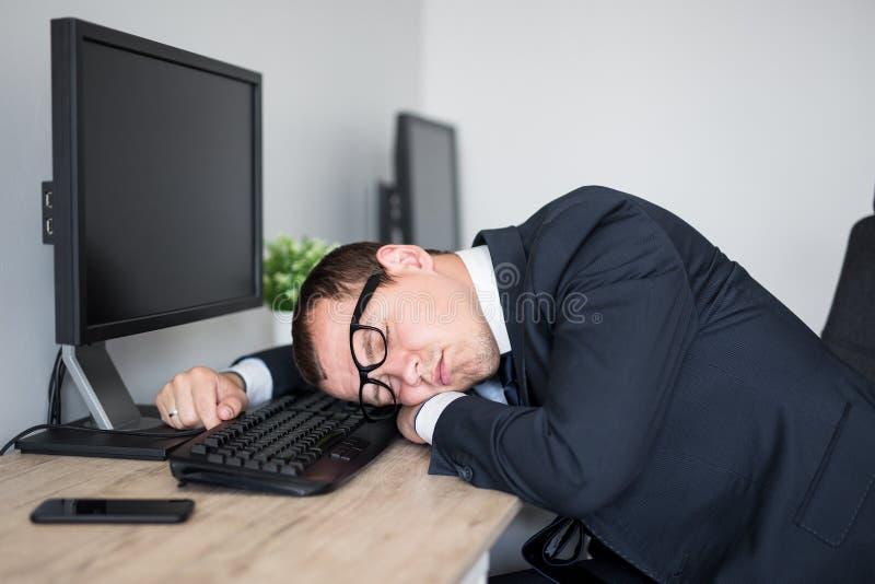Vermoeide zakenmanslaap op de lijst in modern bureau stock afbeelding
