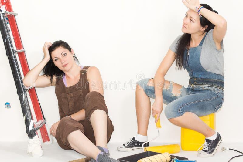 Vermoeide zusters die terwijl het opknappen rusten stock foto