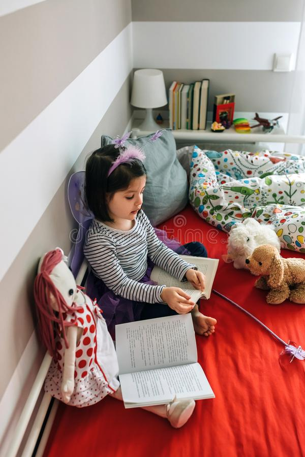 Vermomd meisje het lezen van een boek aan haar speelgoed stock fotografie