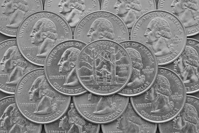 Vermont State and coins of USA. Pile of the US quarter coins with George Washington and on the top a quarter of Vermont State stock image