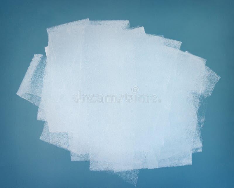 Vernice bianca. Brushstrokes sulla parete blu immagine stock libera da diritti