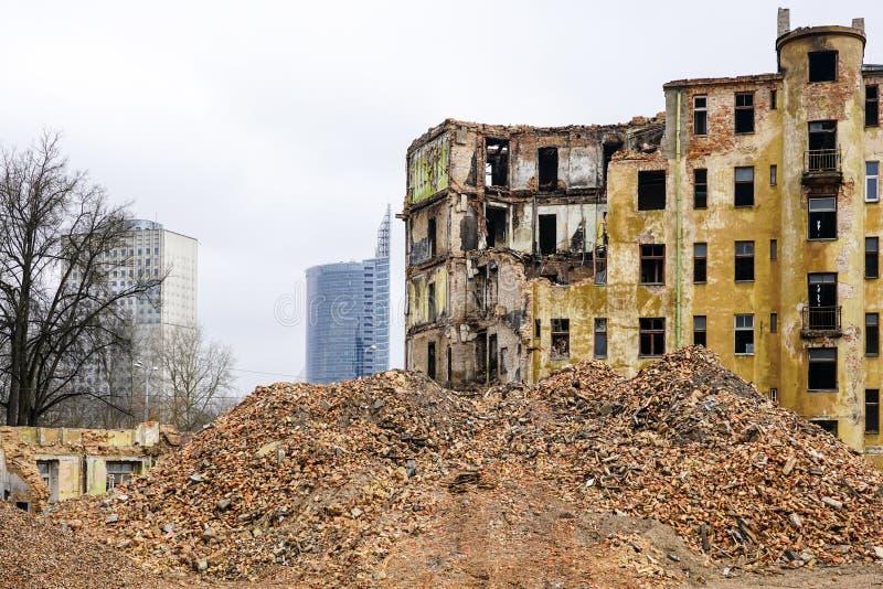 Vernieling van een groot oud historisch steenhuis in de stad, nieuwe gebouwen met meerdere verdiepingen op de achtergrond stock foto's
