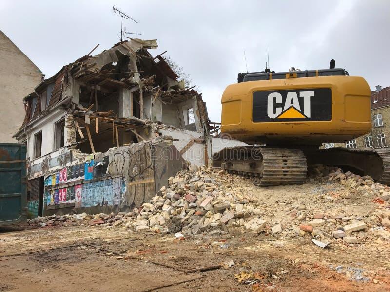 Vernieling van een oud huis met gele de machtsschop van het kattengraafwerktuig voor de bouw van nieuwe flats stock afbeeldingen