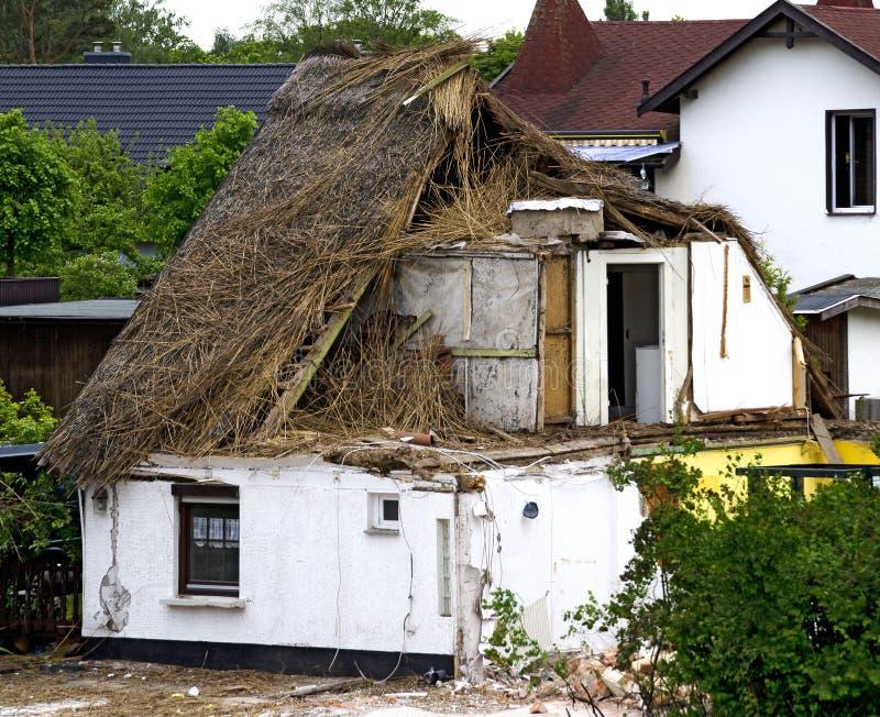 Vernieling van een riet behandeld huis stock afbeeldingen