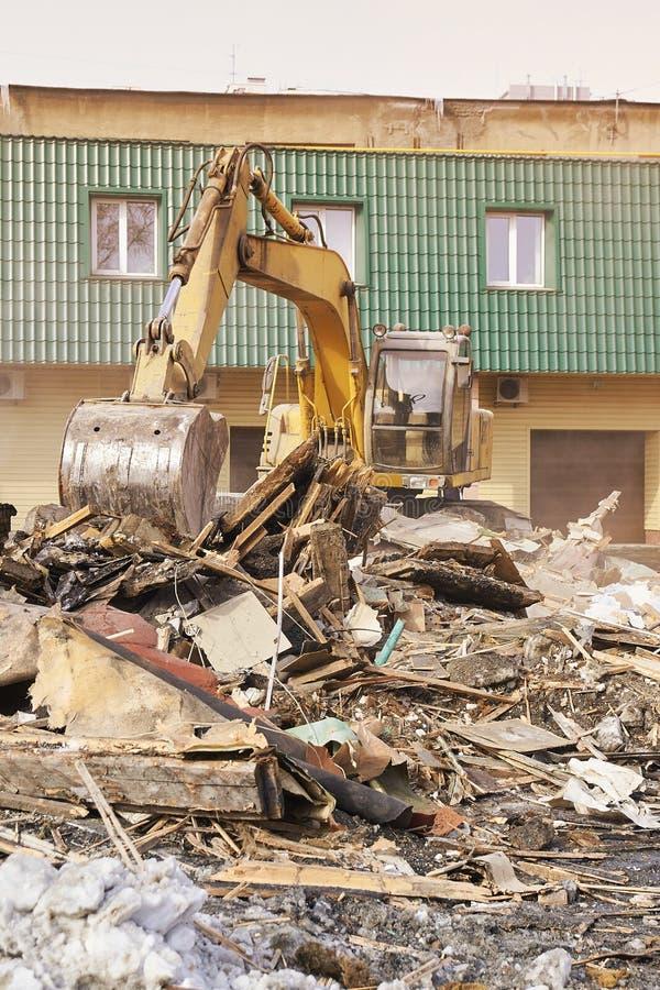 Vernielingshuis die graafwerktuig in stad met behulp van Het herbouwen van proces Verwijder materiaal stock foto