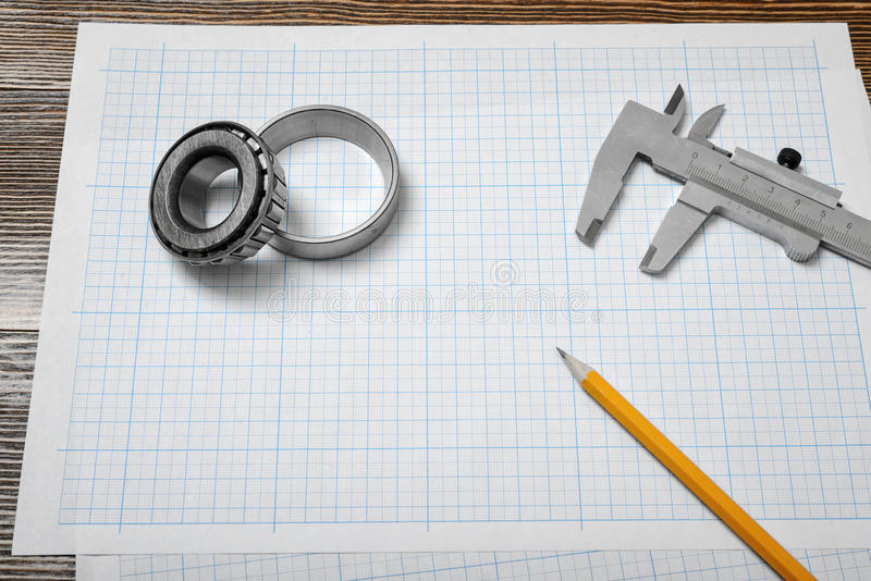 A vernier caliper holding a bearing, a pencil and a pair of compasses lying over drafting paper on wood background. royalty free stock photography