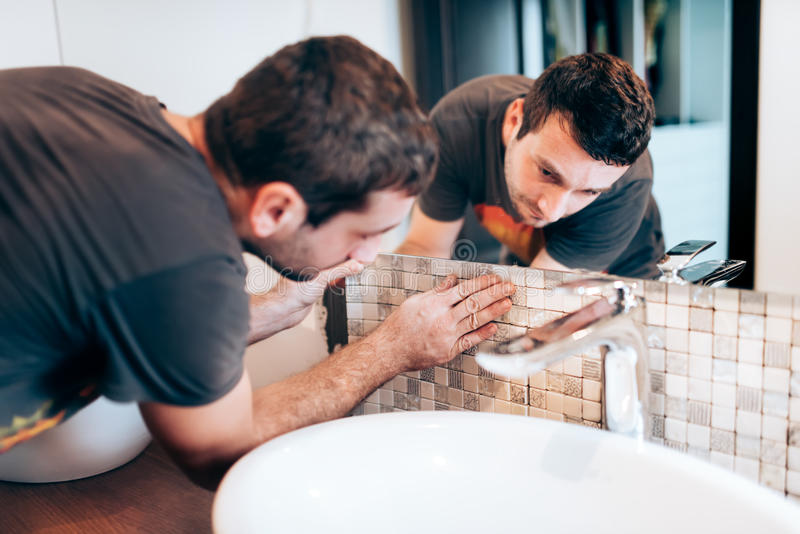 vernieuwingsdetails Bouwdetails met manusje van alles of arbeider die mozaïekkeramische tegels op badkamersmuren toevoegen stock afbeelding