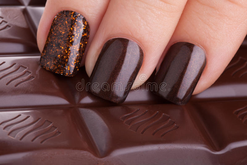 Vernis à ongles de Brown sur les ongles image stock