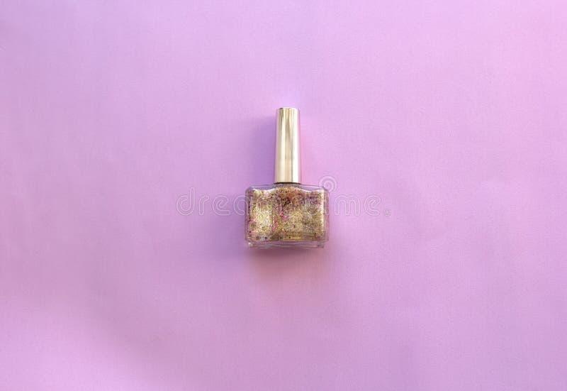 Vernis à ongles des femmes dans la bouteille en verre sur le fond rose Vue sup?rieure, configuration plate photos stock