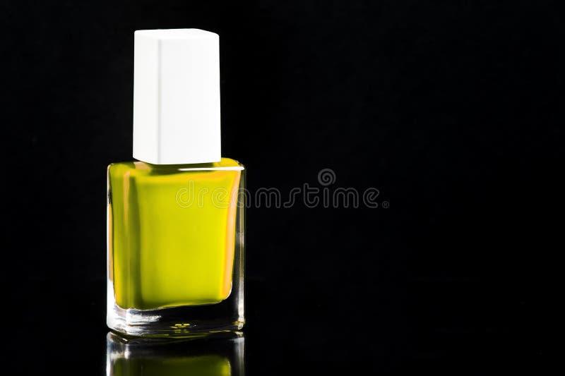 Verniz para as unhas de néon do verde-lima no fundo preto lustroso isolado garrafa, espaço da cópia, foco seletivo foto de stock royalty free