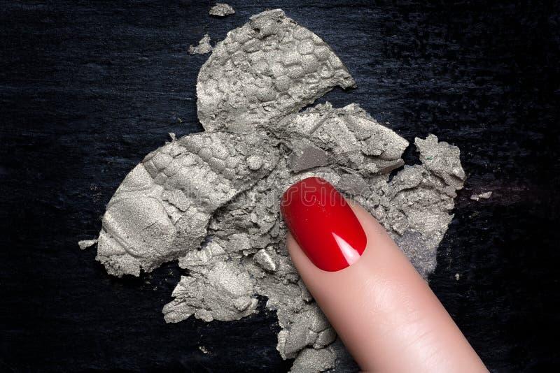 Verniz para as unhas vermelho e sombra para os olhos de prata mineral foto de stock royalty free