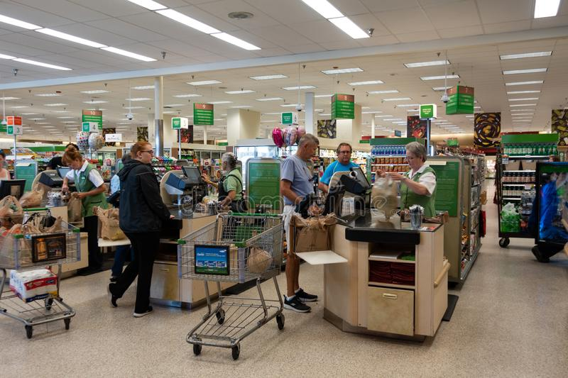 Employees checking out customers at a grocery store royalty free stock photo