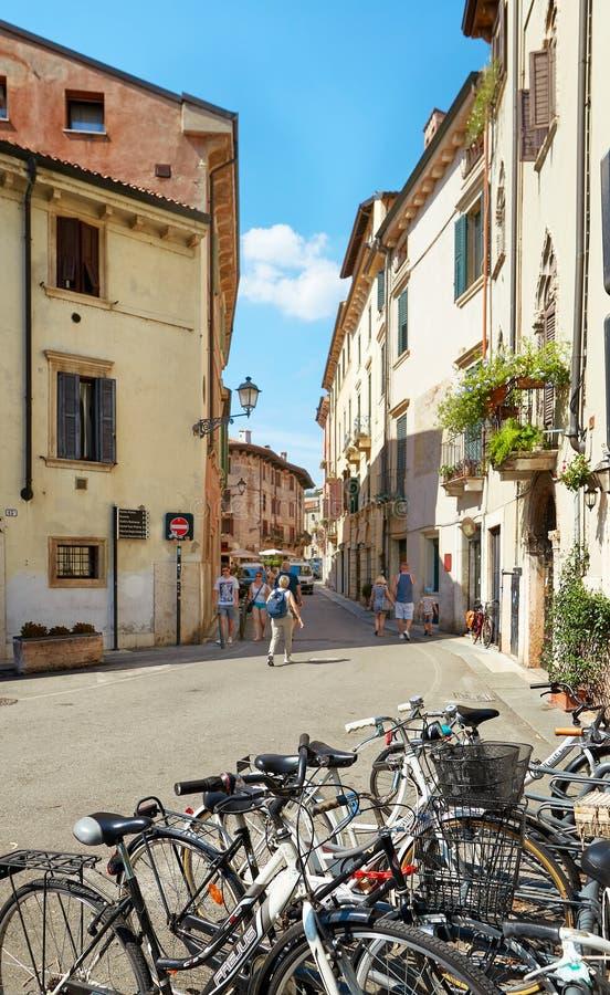 VERONA, ITALIA - 17 AGOSTO 2017: Via stretta di Verona con le biciclette parcheggiate fotografia stock