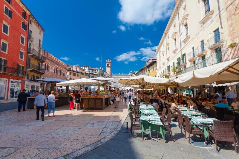 VERONA, ITALIA 8 de septiembre de 2016: Frutas de compra de la gente en el mercado local y turistas en el café en el delle Erbe d imágenes de archivo libres de regalías