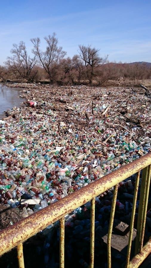 Verontreiniging met plastic afval op een rivier stock foto