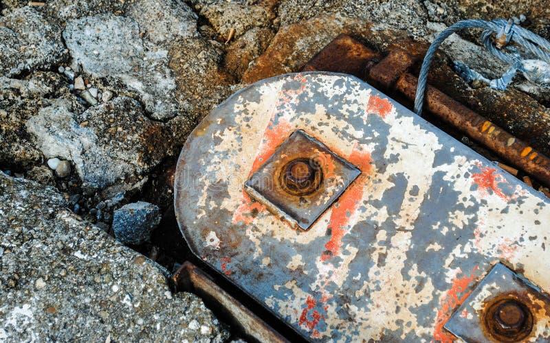 Verontrust metaal in concrete grond stock foto