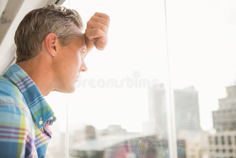 Verontruste toevallige zakenman die tegen venster leunen royalty-vrije stock foto's