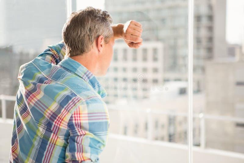 Verontruste toevallige zakenman die tegen venster leunen royalty-vrije stock fotografie