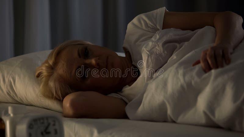 Veroordeelde en hopeloze vrouw in depressie die in haar bed bij verpleeghuis, het verouderen liggen royalty-vrije stock foto