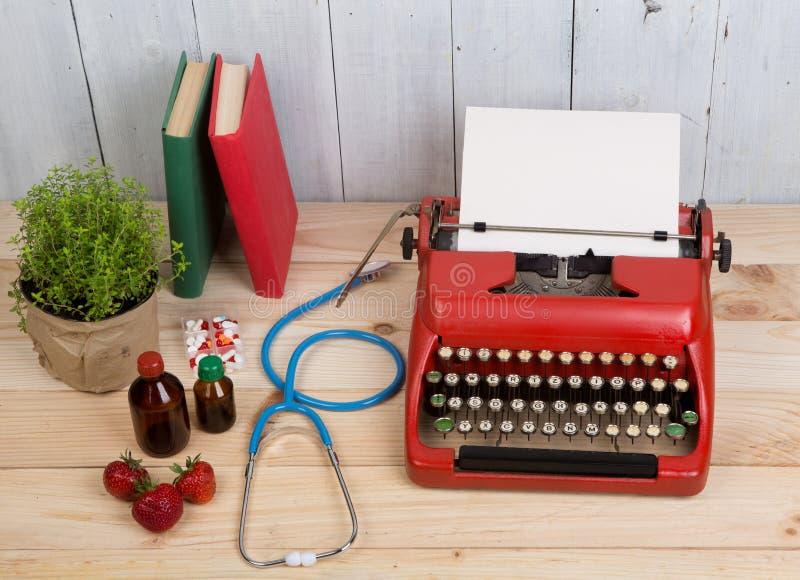 Verordnungsmedizin oder medizinische Diagnose - Doktorarbeitsplatz mit blauem Stethoskop, Pillen, rote Schreibmaschine, Erdbeeren lizenzfreie stockbilder