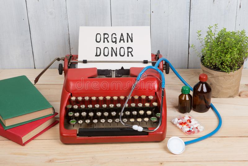 Verordnungsmedizin oder medizinische Diagnose - Doktorarbeitsplatz mit Stethoskop, Pillen, Schreibmaschine mit Text Organ-Spender stockfoto