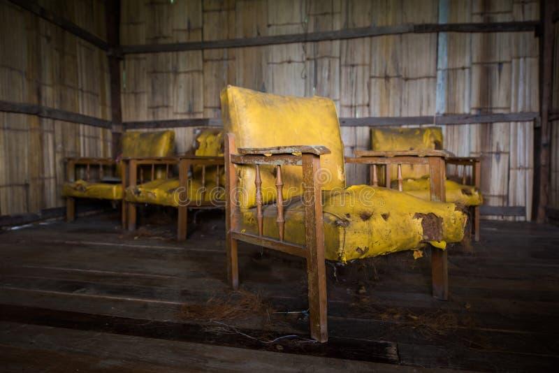 verouderde oude gele leerstoel in ongedwongenheidshuis stock foto's