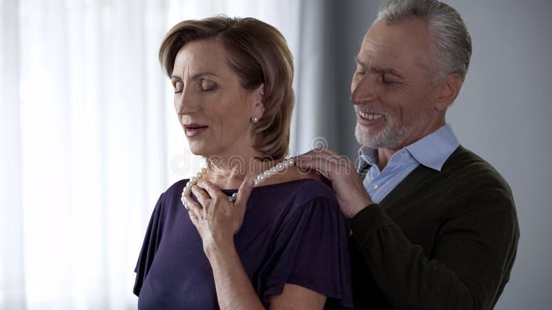 Verouderende echtgenoot die parelhalsband op vrouw opgetogen met juwelen, verrassing zetten royalty-vrije stock afbeeldingen