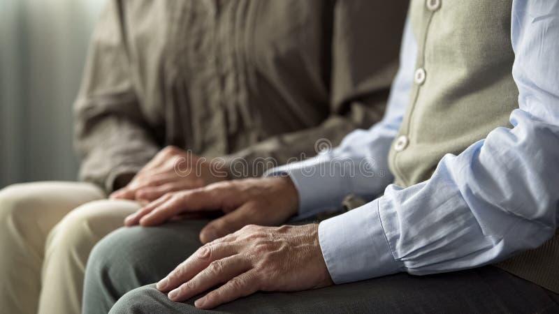 Verouderende echtgenoot en vrouwenzitting samen bij bank, steun en het begrip stock afbeelding