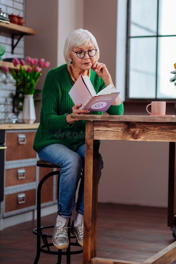 Verouderende vrouw die in boekzitting bij geleverde keuken worden geabsorbeerd royalty-vrije stock afbeelding