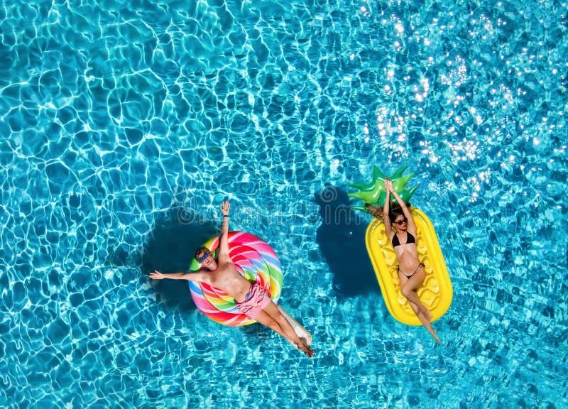Verpaarung auf aufblasbaren Schwimmschwimmschwimmschwimmschwimmen über blaues Wasser des Schwimmbades stockfotografie