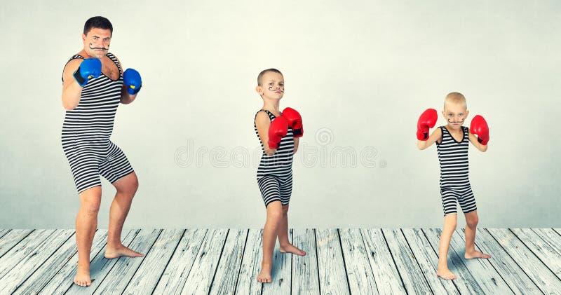 verpacken Vater und zwei Söhne in den Weinlesekostümen spielen Boxer Verpackenfamilie lizenzfreie stockfotografie