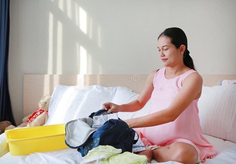 Verpackende Babykleidung der schwangeren asiatischen Mutter für das Gehen zum Krankenhaus in wenige Tage stockbild