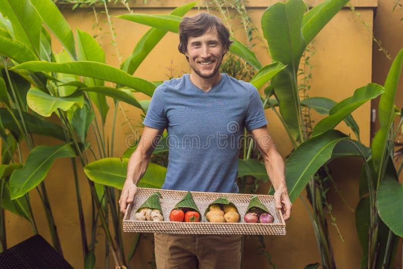 Verpackenkonzept des umweltfreundlichen Produktes Gemüse wickelte in einem Bananenblatt, als Alternative zu einer Plastiktasche e stockfoto