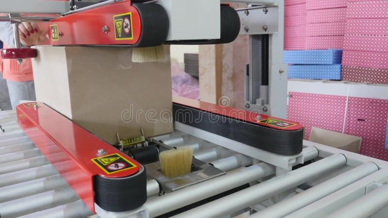 Verpackmaschine an der Werkstatt von Lebensmittelfabrik Prozess der Verpackungssüßigkeit im Folienpaket Arbeiter Automated lizenzfreies stockfoto