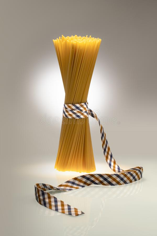 Verpackte Modespaghettis gebunden mit Band auf zweifarbigem Hintergrund stockbilder