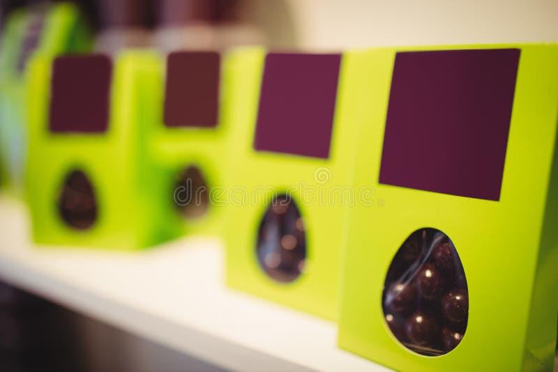 Verpackte Schokoladen im grünen Kasten in der Anzeige stockbilder