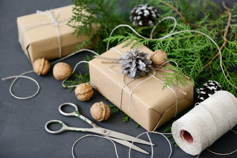 Verpackung von rustikalen eco Weihnachtsgeschenken mit Kraftpapier, Schnur und natürlichen Tannenzweigen auf dunklem Hintergrund stockfotos