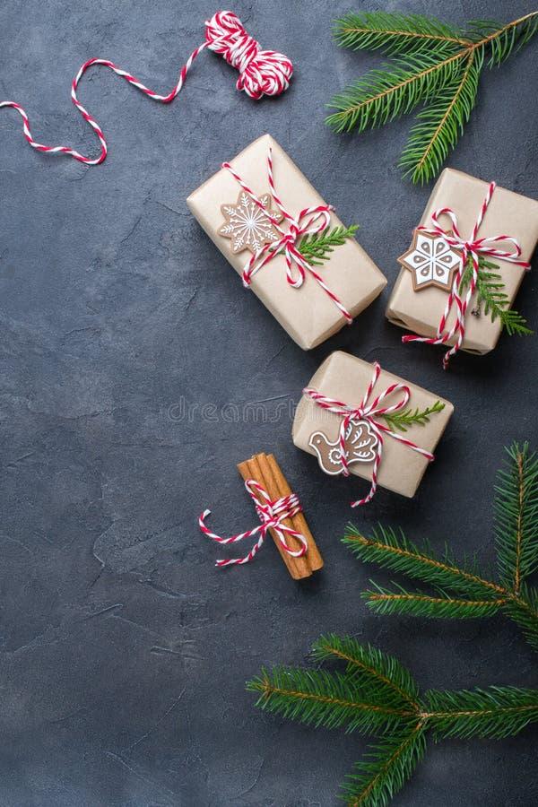 Verpackungs-Weihnachtsgeschenke Weihnachtsgeschenkboxen und Dekorationen, Kiefernniederlassungen auf dunkler Tabelle Geschenk ver lizenzfreies stockbild