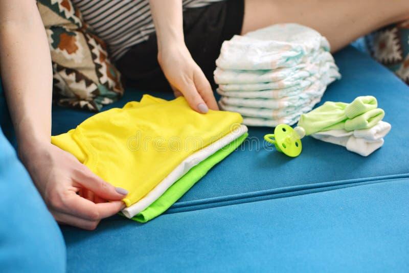 Verpackungstasche der schwangeren Frau f?r Geburtsklinik zu Hause Werdende Mutter faltet Kleidung für ein neugeborenes stockfotos