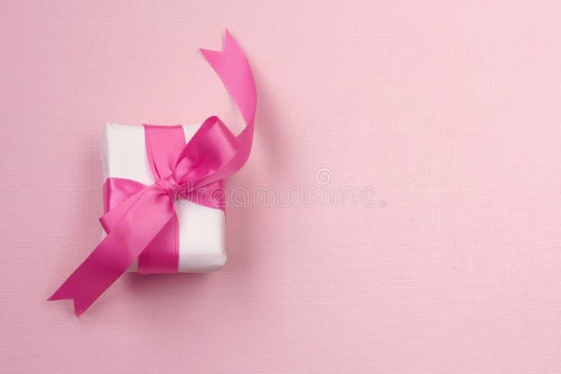 Verpakt giftvakje met roze boog, op document textuurachtergrond stock foto