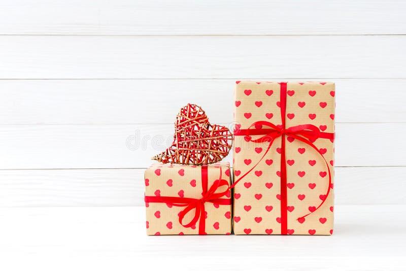 Verpakte giftendozen en rood hart op witte houten achtergrond De ruimte van het exemplaar royalty-vrije stock afbeeldingen