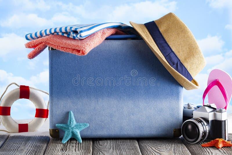 Verpakte koffer voor zomervakanties, hoed, fotocamera en flip op houten tafel stock fotografie
