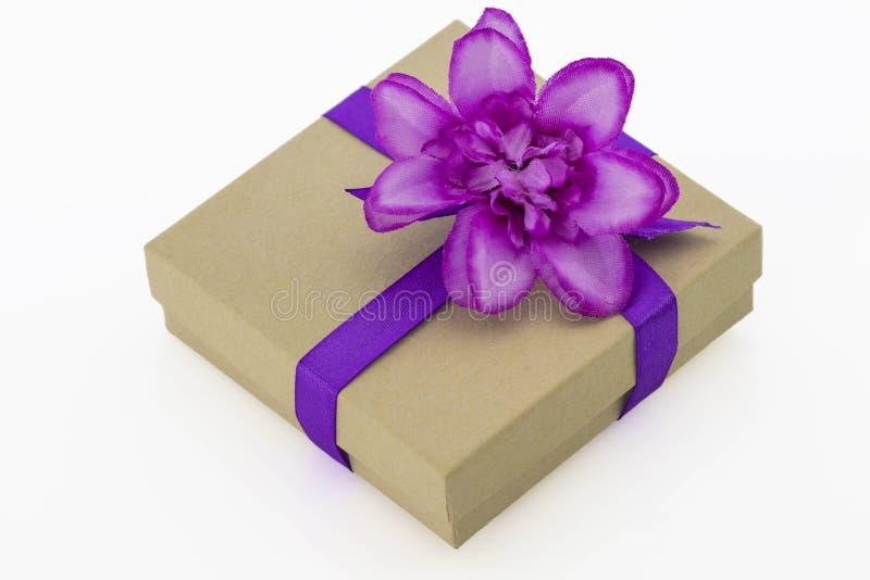 Verpakte uitstekende giftdoos met purper lint en geïsoleerde bloem stock fotografie