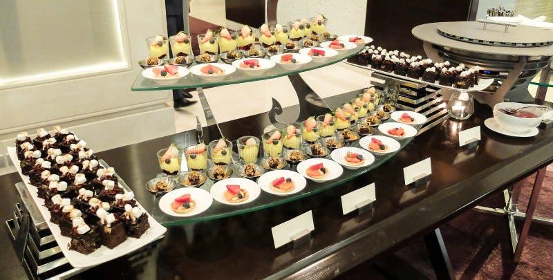 Verpflegungs-Nachtisch und Bäckerei auf Buffet-Linie mit orange Sun-Licht-Schatten an der Ecke, selektiver Fokus im mittleren, In lizenzfreie stockbilder